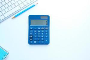 close-up van blauwe rekenmachine en toetsenbord op witte achtergrond