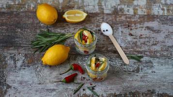 gefermenteerde citroenen in potjes zout, chilipeper en rozemarijn foto