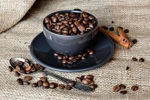 zwarte koffiemok vol biologische koffiebonen en kaneelstokjes op linnen doek