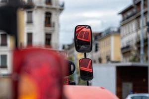 close-up van de zijspiegel van de tractor op onscherpe stadsachtergrond. de spiegel toont de rode motorkap van de tractor.