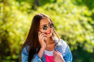 mooie, emotionele, jonge vrouw in zonnebril praten aan de telefoon foto