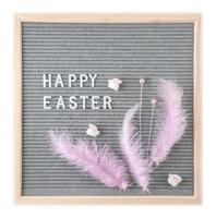 letterbord met tekst vrolijk Pasen met roze veren en speelgoedkonijnen