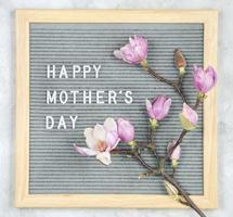 letterbord met witte plastic letters met het citaat gelukkige moederdag en magnoliabloemen op grijze marmeren achtergrond foto