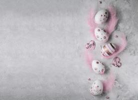 Pasen-beschilderde eieren en roze veren op een grijze marmeren achtergrond