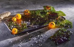 knapperig nori zeewier met cherrytomaatjes en donkere kruiden op grijs beton foto