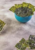 knapperig nori zeewier in een blauwe kom op een grijze achtergrond