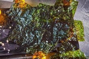 knapperig nori zeewier met cherrytomaatjes en donkere kruiden op grijs beton