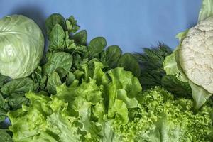 vegetarisch groen dieet van kool, bloemkool, sla en spinazie op een blauwe achtergrond foto
