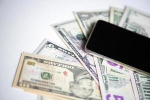 dollar biljetten en zwarte smartphone op witte achtergrond, bovenaanzicht