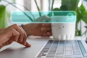 een hand die een laptopcomputer gebruikt die naar informatie op internet zoekt met een zoekvakpictogram foto