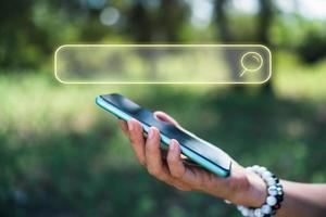 iemands hand met behulp van een smartphone met een zoekvakpictogram op een wazige achtergrond van de natuur foto