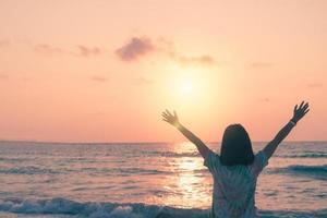 een vrouw die tijdens de zomervakantie haar handen opheft naar de hemel op een strand