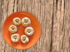 koekjes op een oranje plaat op een houten tafel achtergrond foto