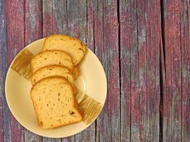 gesneden brood op een keramische plaat op een houten tafel achtergrond foto
