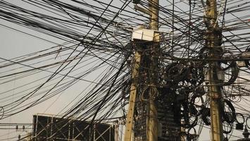 communicatielijnen die er rommelig uitzien op elektrische palen foto