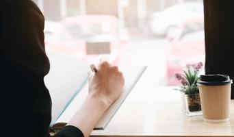 vrouw schrijven in een notitieblok aan een bureau foto