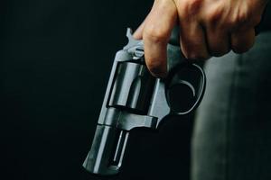 zwarte revolver met een trommel in de hand van een man foto