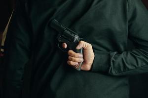 een man met een revolver achter zijn rug foto