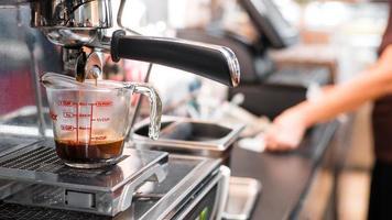 espresso wordt gegoten in een maatbeker