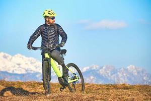 man pauzeert op een mountainbike om de scène in zich op te nemen foto