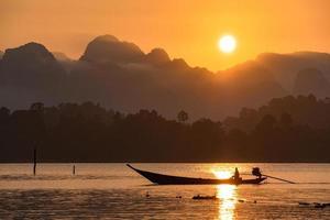 silhouetbeeld van een boot die in een dam in het zuiden van Thailand vaart foto