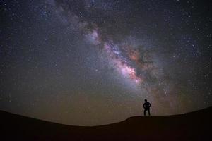 melkwegstelsel met een man die staat en kijkt naar de teerwoestijn, jaisalmer, india foto