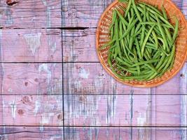 sperziebonen op een rieten plaat op een houten tafel achtergrond foto