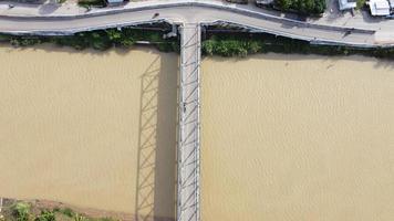 Bekasi, Indonesië 2021 - luchtfoto van een drone van een lange brug aan het einde van de rivier die twee dorpen met elkaar verbindt foto