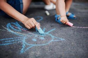 close-up van kinderen tekenen met krijt op de stoep foto