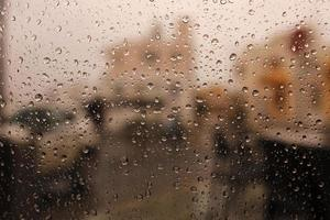 regendruppels op een raam met gebouwen op de achtergrond