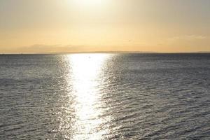 zonsondergang reflectie op kalme zee foto