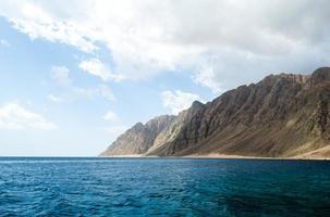 blauwe zee en hoge rotsachtige bergen foto