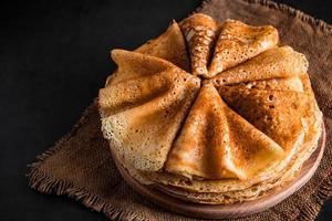 stapel heerlijke pannenkoeken op een zwarte achtergrond foto