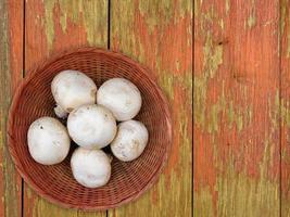 witte champignons op een rieten plaat op een houten tafel achtergrond foto