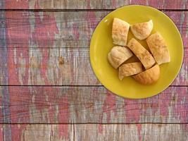 gesneden brood op een gele plaat op een houten tafel achtergrond foto