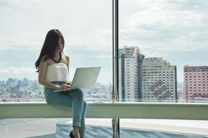 vrouw met laptopcomputer voor grote stadsgezicht raam