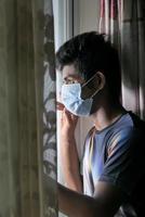 man met een masker kijkt uit het raam