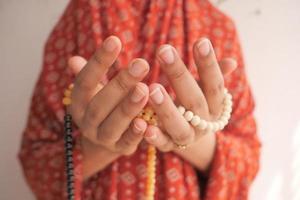 close-up van handen bidden met kralen foto