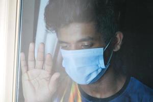 man met masker en kijkt door een raam
