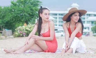 twee mooie vrouwen die gelukkig op het strand zitten