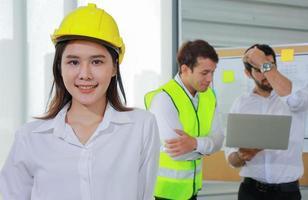 jonge ingenieur die een gele helm draagt, glimlacht vol vertrouwen voordat hij aan het werk gaat