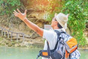 Aziatische reiziger steekt met plezier zijn hand op om frisse lucht in te ademen terwijl hij de natuur bestudeert