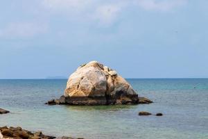 rots in het midden van de tropische zee foto