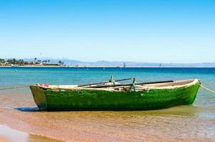 oude groene boot in het water foto