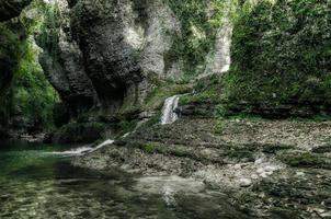 kleine waterval die naar een beek leidt foto