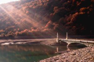 zonlicht op een stenen brug over een rivier foto