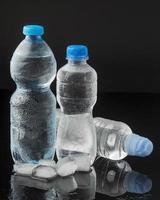 ijsblokjes flessen water, vooraanzicht foto
