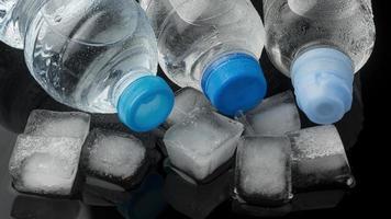 ijsblokjes en flessen water, vooraanzicht foto