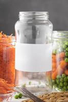 vooraanzicht van ingemaakte erwten en baby worteltjes in helderglazen potten foto