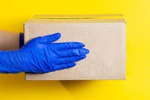 een man in latexhandschoenen bezorgt een pakket op een gele achtergrond